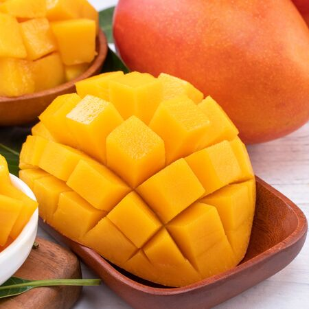 Photo for Fresh chopped mango on a tray and bright rustic wooden background. Tropical summer fruit design concept, close up, macro, copy space. - Royalty Free Image