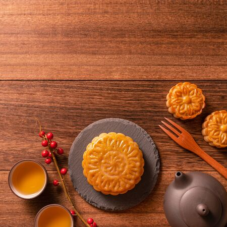 Photo pour Chinese traditional pastry Moon cake Mooncake with tea cups on bamboo serving tray on wooden background for Mid-Autumn Festival, top view, flat lay. - image libre de droit