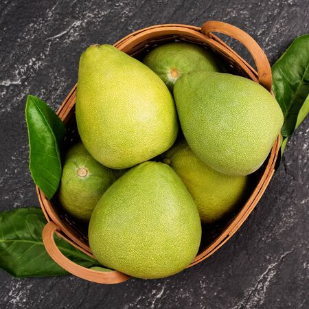 Photo pour Fresh pomelo,grapefruit in bamboo basket with green leaf on dark black slate background. Seasonal fruit for Mid-Autumn Festival. Top view. Flat lay. - image libre de droit
