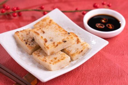 Photo pour Chinese lunar new year food concept, Delicious turnip radish cake, local cuisine in restaurant with soy sauce on red background, close up, copy space - image libre de droit