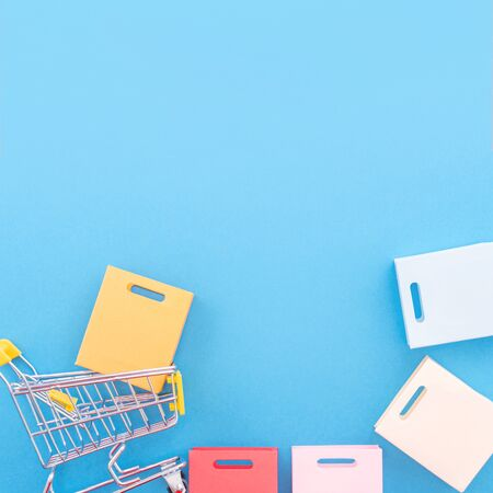 Photo pour Abstract design element, annual sale, shopping season concept, mini yellow cart with colorful paper bag on pastel blue background, top view, flat lay - image libre de droit