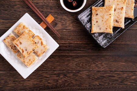Foto de Delicious turnip cake, Chinese traditional radish cake in restaurant with soy sauce for new year's dishes, close up, copy space, top view, flat lay. - Imagen libre de derechos