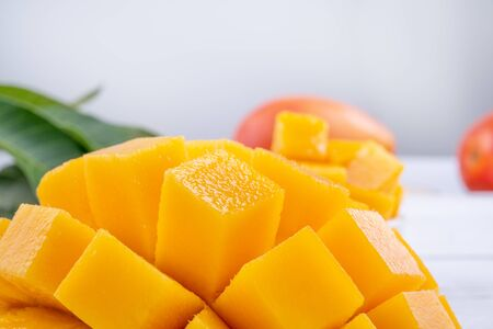 Photo for Fresh mango,beautiful chopped fruit with green leaves on bright wooden table background. Tropical fruit design concept, close up, copy space. - Royalty Free Image