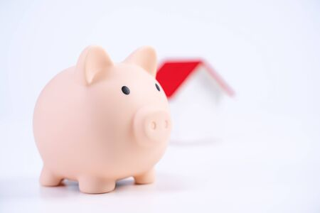 Photo pour Financial concpet - Piggy bank, beautiful red white wooden house model on white background, saving money to buy insurance, close up, copy space. - image libre de droit