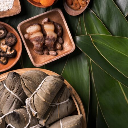 Photo for Rice dumpling, zongzi - Traditional Chinese food on green leaf background of Dragon Boat Festival, Duanwu Festival, top view, flat lay design concept. - Royalty Free Image