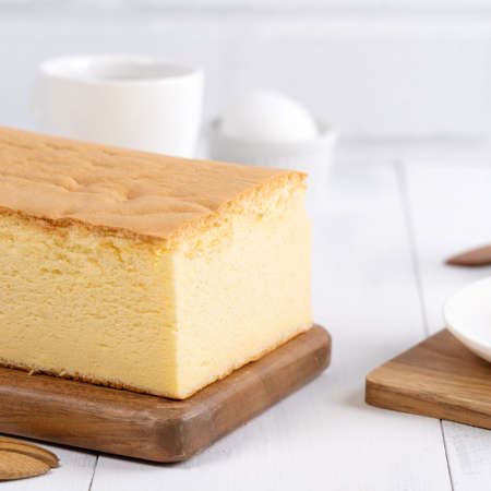 Photo pour Plain classic Taiwanese traditional sponge cake (Taiwanese castella kasutera) on a wooden tray background table with ingredients, close up. - image libre de droit