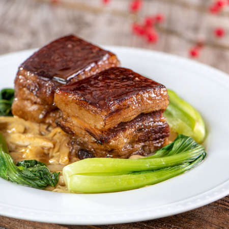 Photo for Dong Po Rou (Dongpo pork meat) in a beautiful blue plate with green broccoli vegetable, traditional festive food for Chinese new year cuisine meal, close up. - Royalty Free Image