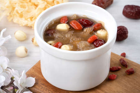 Photo pour Close up of traditional Chinese sweet snow white fungus soup with lotus seed, red dates (jujube) and wolfberry (goji, gojiberry) on white background. - image libre de droit