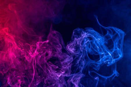 Foto de Conceptual image of colorful red and blue color smoke isolated on dark black background, Halloween concept design element. - Imagen libre de derechos
