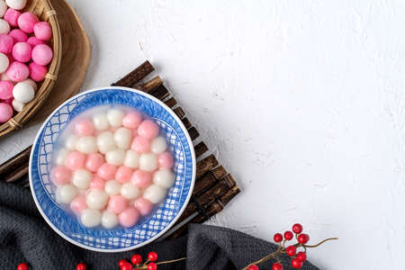 Photo for Top view of red and white tangyuan (tang yuan, glutinous rice dumpling balls) in blue bowl on white background for Winter solstice festival food. - Royalty Free Image