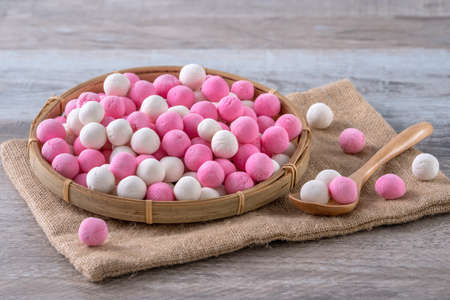 Photo for Raw red and white tangyuan glutinous rice dumpling balls on wooden table background for Winter solstice festival food. - Royalty Free Image
