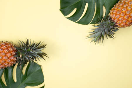 Photo pour Top view of fresh pineapple with tropical palm and monstera leaves on yellow table background. - image libre de droit