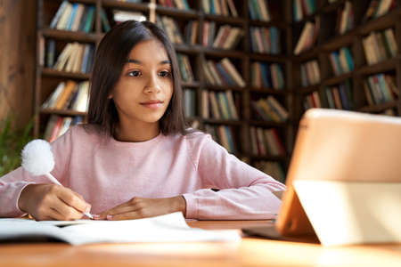 Foto de Indian lating school girl learning online class watching video lesson on tablet. - Imagen libre de derechos