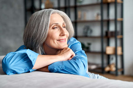 Photo for Happy relaxed mature old woman resting dreaming sitting on couch at home. - Royalty Free Image