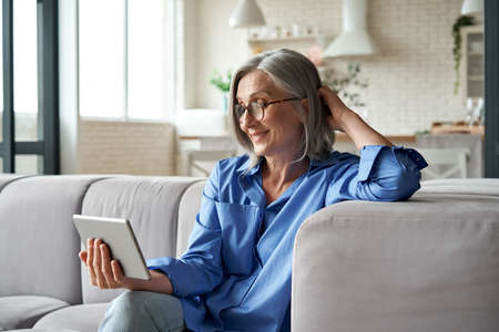 Photo pour Happy 60s mature woman calling or watching video digital tablet at home. - image libre de droit