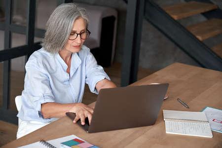 Photo pour Older mature middle aged woman using laptop computer sitting at work desk. - image libre de droit