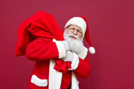 Photo for Tired Santa Claus feeling back pain holding heavy bag on red background. - Royalty Free Image