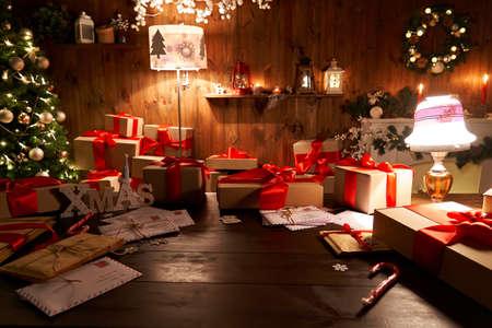 Photo pour Santa workshop table with Merry Christmas tree, gift boxes pile on xmas night. - image libre de droit