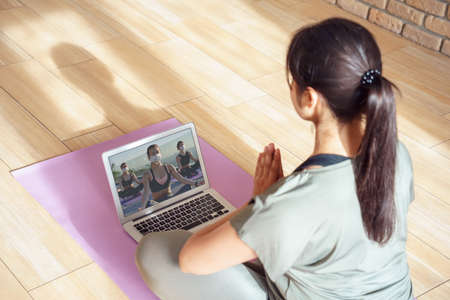 Photo pour Young woman meditating watching online yoga class video tutorial at home. - image libre de droit