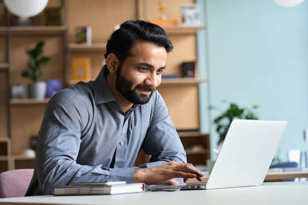 Photo pour Smiling indian business man working studying on laptop computer at home office. - image libre de droit