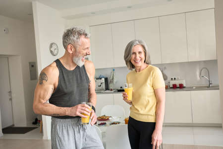 Photo for Healthy sporty happy seniors family couple drinking juice and laughing at home. - Royalty Free Image