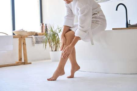 Photo pour Middle aged mature woman applying veins creme on legs sitting in bathroom. - image libre de droit