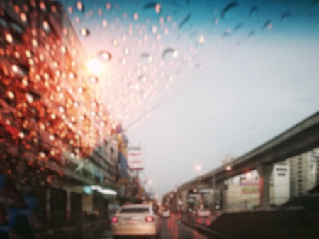 Blur street traffic in twilight after rain (Thailand); wet car glass (clear with blue color on top) from raindrops and dried part from windshield wiper. Skytrain rail on the right. Top copy-space.