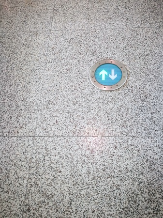 Green arrows sign on granite floor in public transport station or airport passenger terminal. There are copy-space on the left and below of image.