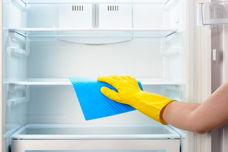Photo for Woman's hand in yellow rubber protective glove cleaning white open empty refrigerator with blue rag - Royalty Free Image