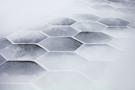 Hexagonal sidewalk tiles covered with snow and ice