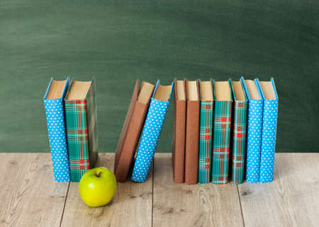Photo for Back to school, pile of books in colorful covers and green apple on wooden table with empty green school board background. Distance home education.Quarantine concept of stay home - Royalty Free Image