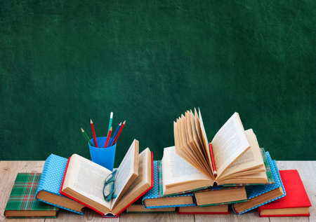 Photo pour Back to school, pile of books in colorful covers and on wooden table with empty green school board background. Distance home education.Quarantine concept of stay home - image libre de droit