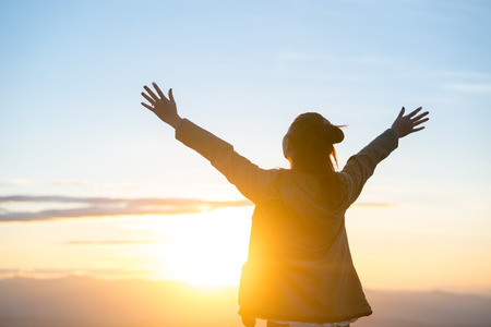 Photo for Happy woman standing alone with arms raised up during beautiful sunrise at the morning. - Royalty Free Image