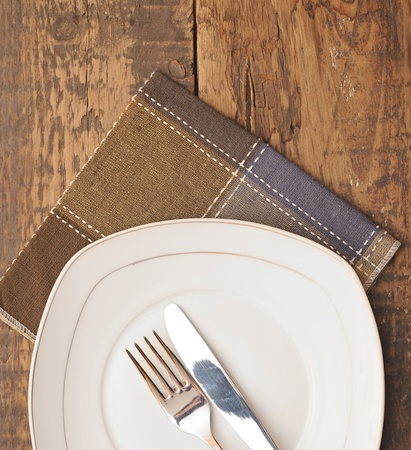 closeup white empty plate with brown napkin, knife and fork on wood table