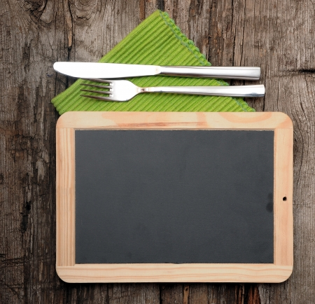 Menu blackboard lying on old  wooden table with knife and fork