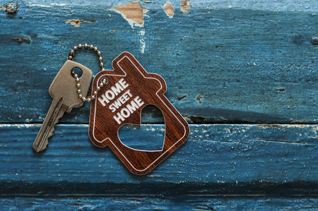 Photo pour House key on a house shaped keychain resting on wooden background, concept for real estate - image libre de droit