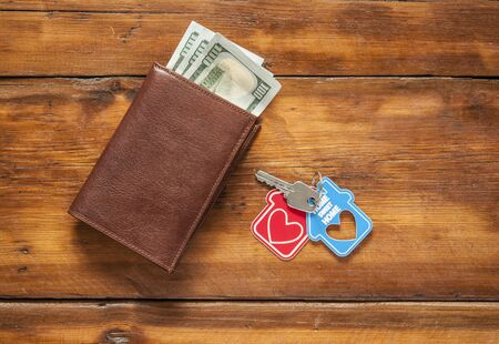 Photo pour Key home and leather wallet on old wooden table.  - image libre de droit