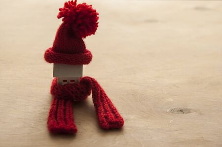 Photo pour House model with knitted hat and scarf on table against white background. Heating concept - image libre de droit