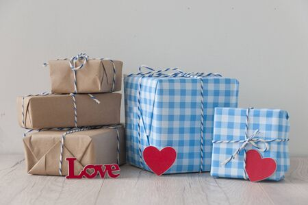 Valentine\'s day background. Cute composition with handmade gift boxes and red hearts on wooden table. Happy birthday or anniversary congratulation. Copy space