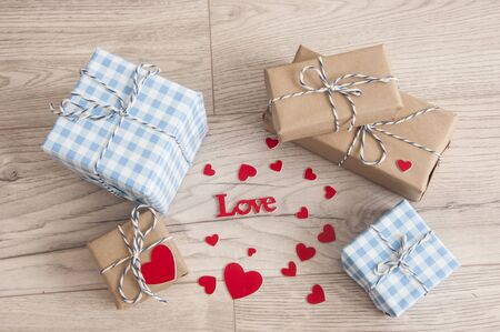 Valentine\'s day background. Cute composition with handmade gift boxes and red hearts on wooden table. Happy birthday or anniversary congratulation. Flat lay, top view, copy space
