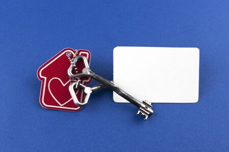 Photo pour Key and house shaped keychain arrangement on blue background. Top view, flat lay. Real estate, insurance concept, mortgage, buy sell house, realtor concept - image libre de droit