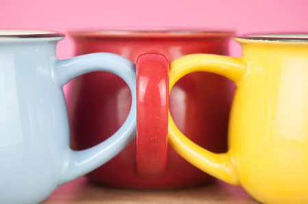 Photo pour three motley cups at wood table background - image libre de droit