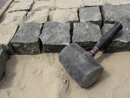 Photo for Black Mallet close-up on a background of square granite stones and sand. The concept of improving the sidewalks and yards - Royalty Free Image