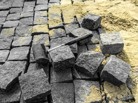 Photo for Laying granite paving stones - building background with copy space. A black rubber mallet lies among gray rectangular blocks of natural stone on the background of yellow sand - Royalty Free Image