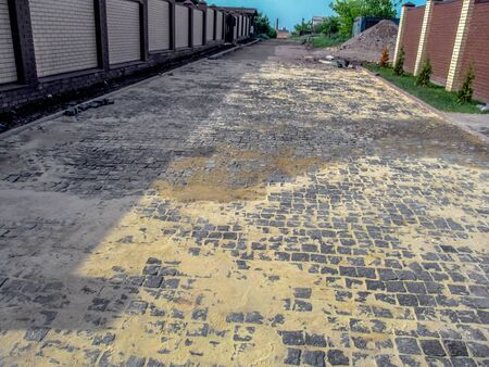 Photo for Road with newly laid granite paving stones covered with sand on a rural street. Landscape with a new stone road among private houses, a distant perspective - Royalty Free Image