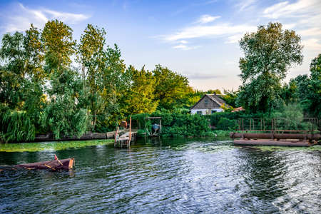 Photo pour View from the water to a settlement on the coast of the Konka River in Kherson (Ukraine). Country house among summer greenery and a private pier in a swampy reservoir - image libre de droit