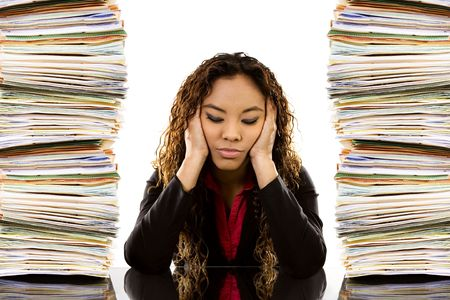 Foto de Stock image of woman sitting at desk with a pile of paperwork on each side - Imagen libre de derechos