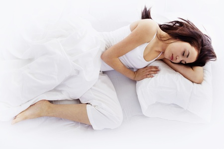 Photo pour Stock image of young woman sleeping on white bed  - image libre de droit
