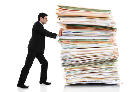 Foto de Stock image of businessman pushing a giant stack of documents isolated on white background - Imagen libre de derechos