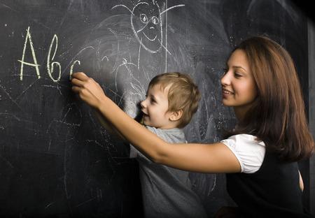 little cute boy with teacher in classroom smiling at blackboard
